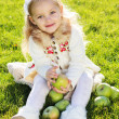 Child with green apples sitting on grass — Stock Photo #54653255
