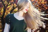 Pretty girl with flying hairs in colorful leaves — Stock Photo