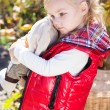 Little girl in warm clothes with toy rabbit — Stock Photo #56063277