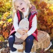 Little girl in warm clothes with toy rabbit — Stock Photo #56063537