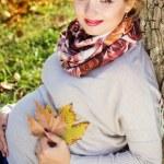 Pregnant girl in autumn park — Stock Photo #56555651