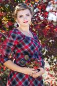 Pregnant girl is wearing checkered dress in park — Stock Photo