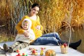 Little boy with her mother on the autumn lake — Stock Photo