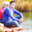 Young couple near lake with pumpkin, autumn time — Stock Photo #57533545