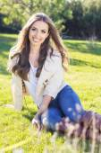 Young pretty teenager girl sitting on green grass — Fotografia Stock