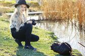 Roztomilá holčička odpočívá nedaleko jezera s fotoaparátem — Stock fotografie