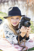 Cute little girl is resting near lake with camera — Stock Photo