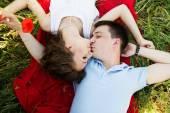 Poppies tam bir çayır üzerinde genç mutlu çift — Stok fotoğraf
