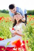 Young happy couple on a meadow full of poppies — Stock Photo