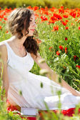 Young beautiful girl in the field of poppies — Stock Photo
