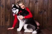 Young girl wearing red dress with her husky dog  — Stock Photo