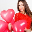 Pretty girl holding red heart balloons — Stock Photo #62253201