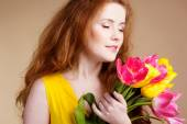 Beautiful redheared girl with bouquet of tulips — Stock Photo