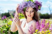 Beautiful girl with a lilac flowers — Stock Photo