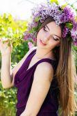 красивая девочка с венком сиреневых цветов — Стоковое фото