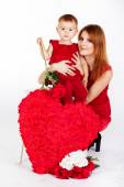 Happy mother and her daughter with big red heart — Stock Photo