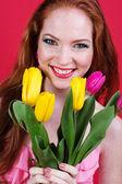 Linda menina ruiva está segurando tulipas — Fotografia Stock