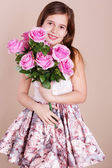 Little girl holding a bouquet of pink roses — Stock Photo