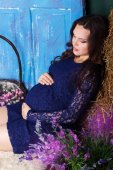Pregnant pretty woman is sitting with hay and flowers — Stock Photo
