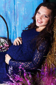 Pregnant woman with flowers in studio — Stock Photo