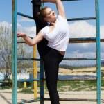 Girl doing stretching exercise near horizontal bar — Stock Photo #72068439
