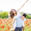 Happy girl and boy on a meadow full of poppies — Stock Photo #72312197