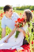 Happy girl and boy on a meadow full of poppies — Stock Photo