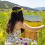 Постер, плакат: Pretty painter girl painting in yellow field
