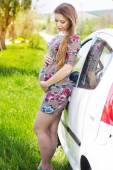 Happy pregnant woman standing near car — ストック写真