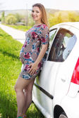 Happy pregnant woman standing near white car — ストック写真
