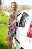 Happy pregnant woman standing near car — Stock Photo