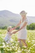 Family mother and child girl in field of daisy flowers — Stock fotografie
