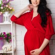 Studio portrait of beautiful pregnant woman in red dress — Stock Photo #75620743