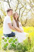 Happy couple sitting on suitcase outdoors — Stock Photo