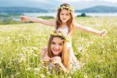 Two pretty girls at meadow with nice mountain view — Stock Photo