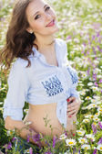 Pretty pregnant woman in daisy flowers field — Stock Photo