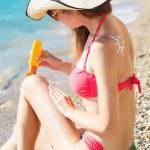 Woman applying sunscreen cream on her legs — Stock Photo #77269420