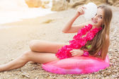 Smiling girl sitting in rubber ring with flowers on neck — Stock Photo