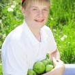 Teen boy is wearing red cap holding apples — Stock Photo #77639128