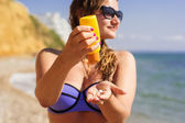 Woman is holding yellow tube with sunscreen tan lotion — Stock Photo