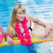 Pregnant blonde woman is lying on mattress in swimming pool — Stock Photo #78112962