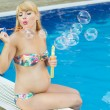 Pregnant girl is making bubbles near swimming pool — Stock Photo #78113258