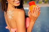 Girl with sun from sunscreen lotion on her shoulder — Stok fotoğraf