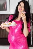 怀孕幸福的女人,在厨房与糖果 — 图库照片
