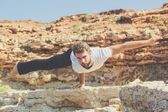 Sportive young man is doing yoga on the beach — Stock Photo