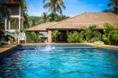 Boy jumped into blue swimming pool and water are splashing. Koh Samui — Stock Photo