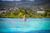 Mujer joven hermosa refrescante en la piscina de verano — Foto de Stock