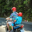 Постер, плакат: Father and son wearing helmets go on a motorbike in Koh Samui