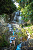 Happy family at a waterfall on the island of Koh Samui — Stock Photo