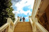 Father and son runs go up the stairs on background of sky — 图库照片